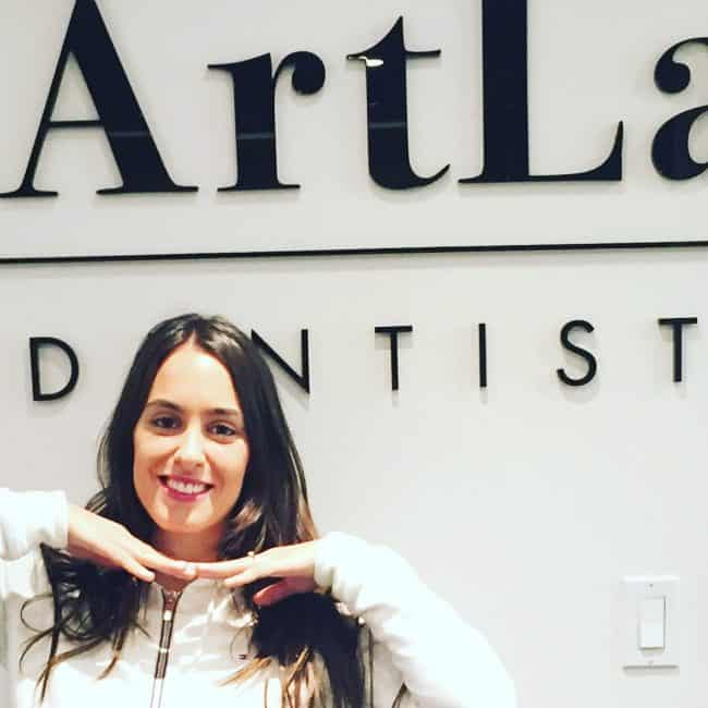 Brunette girl smiling after front tooth restoration and standing in front of ArtLab Dentistry sign